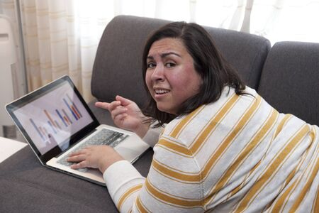 Woman at home points at her laptop showing a bar chart with results that are confusing