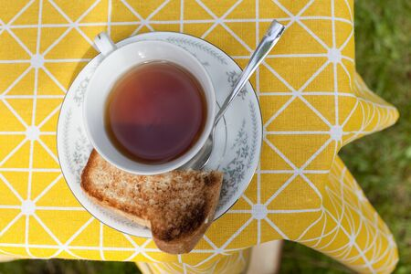 Downward view into a teacup with saucer, spoon and toast