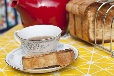 A red teapot with a cup and saucer and toasted bread