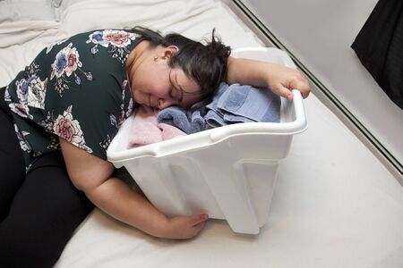 Latina woman has fallen asleep in a basket with several colorful folded towels Stock fotó