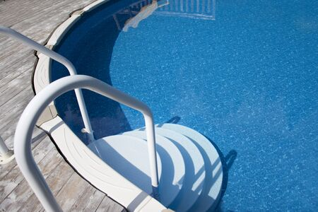 Backyard pool on a hot day beside a deck, with a staircase Фото со стока