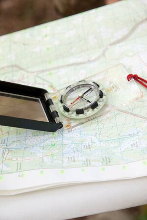 Old school navigation with paper map and digital compass outside in the woods Фото со стока
