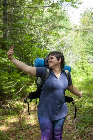 woman taking self portrait in the woods while hiking or camping 写真素材