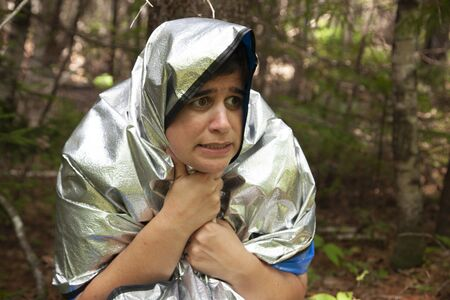 person in a blanket trying to keep warm while waiting for rescue in the woods