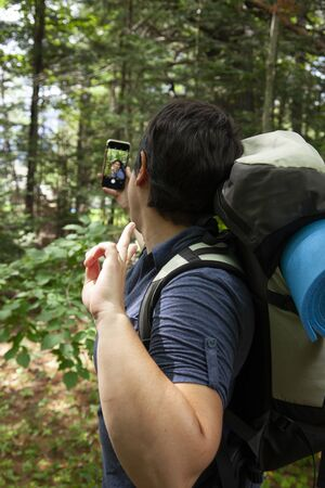 person stops for a social media selfie while hiking in the woods