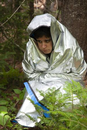 person wrapped in a tinfoil blanket looks scared, cold and lost in the woods