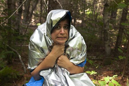 person wearing a space blanket in the woods to keep warm while they are lost makes an afraid expression