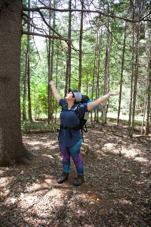 Person outside in the woods smiling with arms open feeling free and happy to be traveling