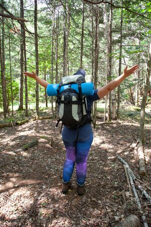 Person standing in the woods in the daytime with arms outstretched welcoming nature