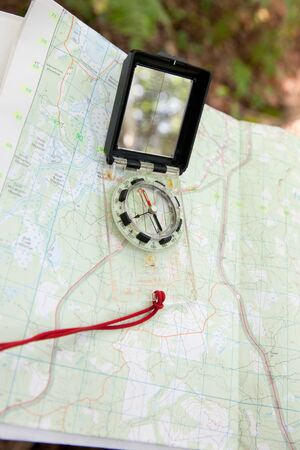 Outside a map with a digital compass shows the direction for a traveler in the forest