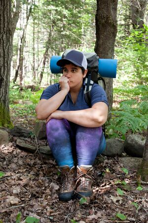 A woman sits on a rock looking puzzled or lost while hiking in the woods