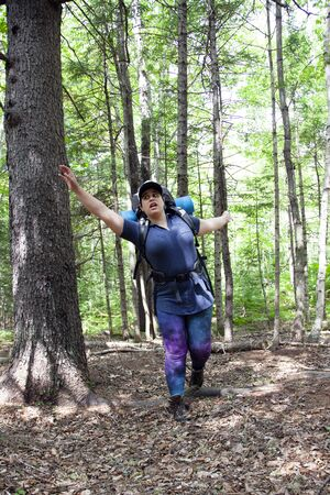 person trips over a root in the forest while hiking or camping