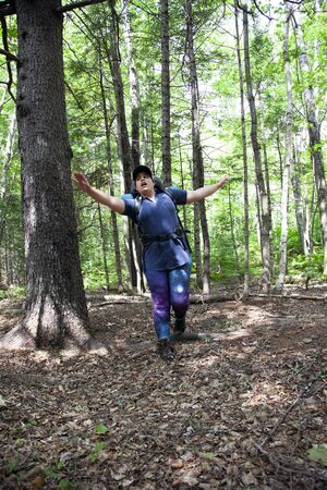 hiker falls over a root in the ground while hiking in the forest