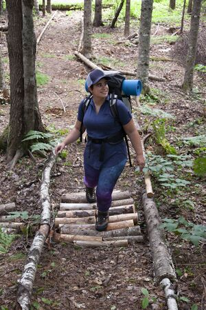 happy woman independently exploring a path in the forest