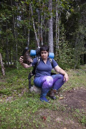 woman sitting on a rock pouring dirt and sand out of her hiking boot looking irritated
