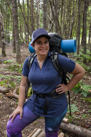 woman in the canadian forest going for a hike with a backpack