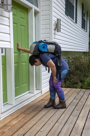 person leaning against their front door with backpack and camping roll after a trip