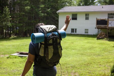 person loking back at their house with a backpack ready for adventure Banco de Imagens