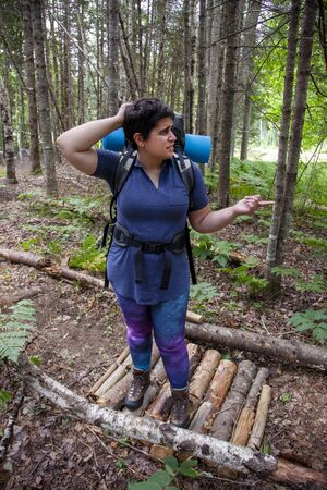 lost camper is puzzled on a path in the woods while hiking