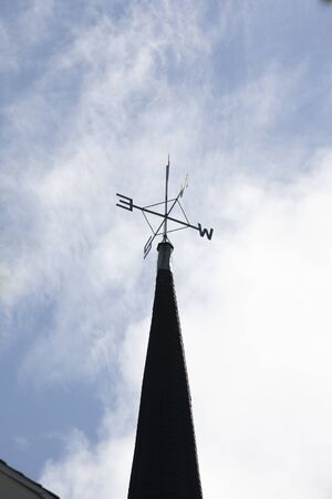 a metal weathervane showing directions on top of a steeple Banco de Imagens