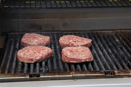raw hamburger meat cooking on the barbeque Banco de Imagens