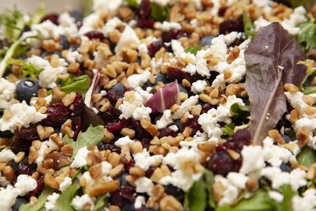 beautiful full looking salad containing feta, blueberries, walnuts and spinach