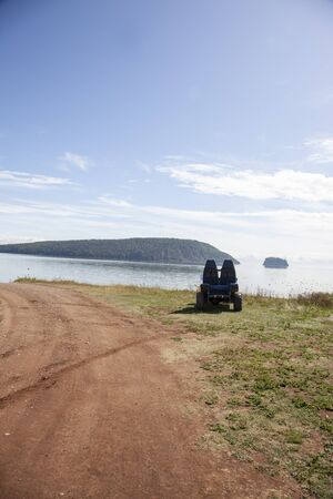 off road terrian vehicle sits by an empty dirt path on the shoreline