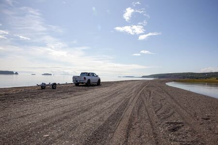 pickup truck on a rocky beach on a summer day Banco de Imagens