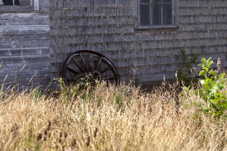 a rusted old cart wheel sitting against the side of an old barn building with tall grass