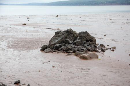 boulders that have fallen into the muddy ocean