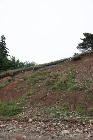 wooden fence falling off the side of an eroding cliff bank due to climate change