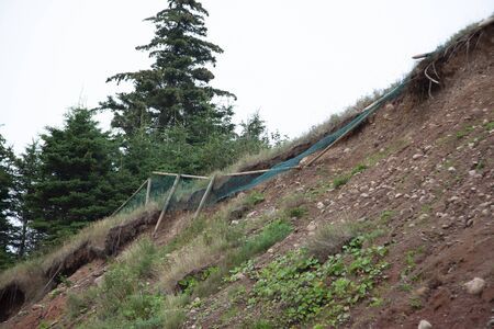 wooden fence with mesh netting has started to fall down the side of a cliff as the rockface erodes