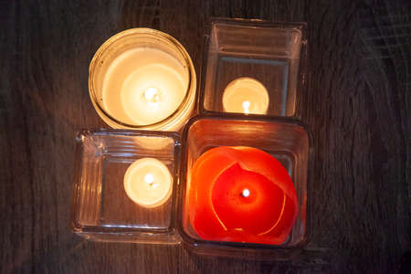 four candles lit and flicker inside glass holders in the darkness Zdjęcie Seryjne