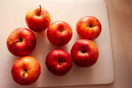 juicy fresh red apples sitting on a white cutting board in the kitchen