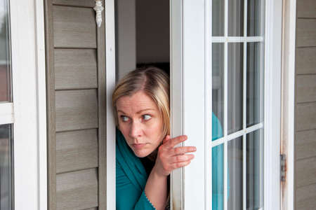 person is scared looking out their front door of their house