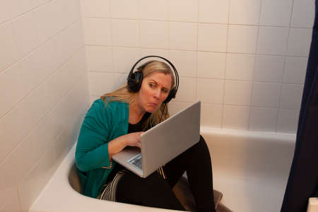 woman gets creative working from home in the bathtub looks suspiciously for interruptions Zdjęcie Seryjne