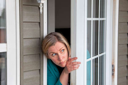 a woman peeks out her front door wondering if it is safe to leave