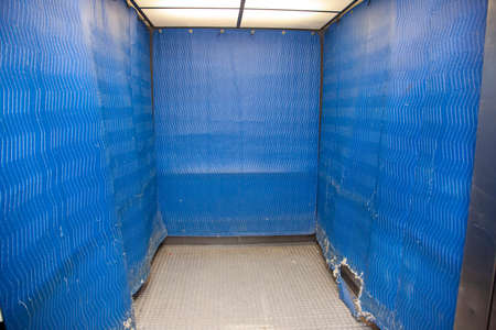 Industrial size elevator with blue protective padding for moving
