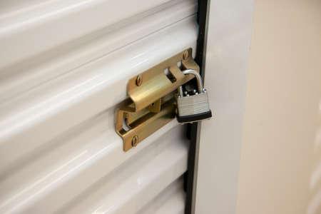 Metal door to an individual storage compartment held shut and locked with a metal padlock
