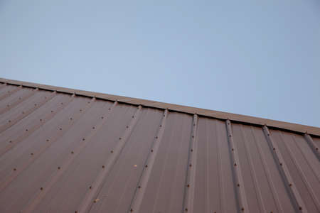 a new metal roof with bolts cuts diagonally across the frame against a clear blue skyline