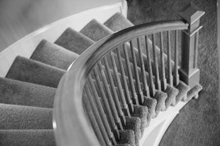 black and white photograph of a beautiful polished wooden railing lining a circular staircase