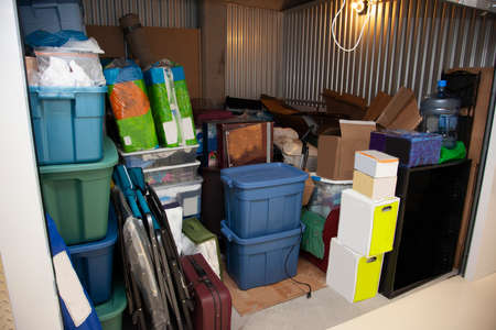 Interior of a self storage unit in a warehouse filled to the brim with belongings and junk