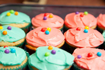 Beautifully frosted colorful cupcakes with candies on top Zdjęcie Seryjne