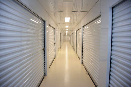 Empty white metal hallway with individual self storage units for personal use