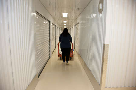 Person going to their metal self storate locker inside a storage unit