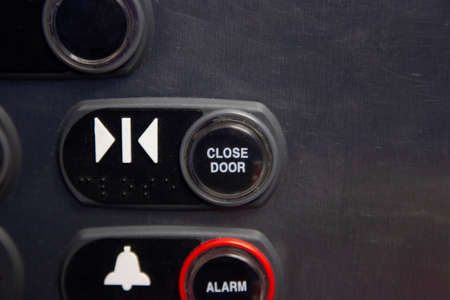 Close view of an elevator button to close the steel door and also elevator alarm button