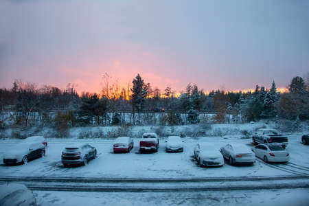 cars parked in a lot outside a building during a frosty beautiful winter sunset