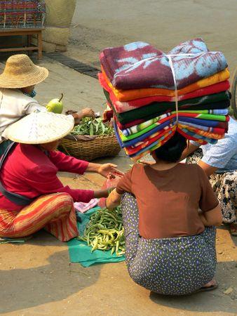 Burma. Lady balancing fabrics. photo