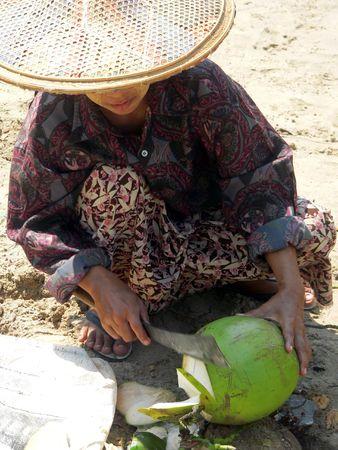 Burma. Beach vedor chopping coconut photo