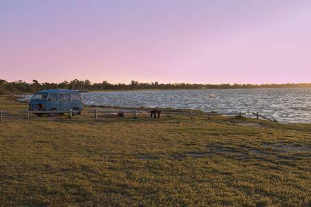 campervan: combi van or campervan  rv on the edge of the lake at sunset